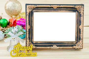 Vintage blank photo frame with christmas decorations on wood bac