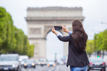Young woman taking a photo with her phone on the Champs Elysees in Paris