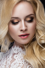 Beautiful blond woman in wedding dress with evening make-up, tender lips and curls. Bride image. Beauty face.