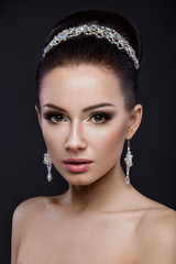 Beautiful brunette girl with perfect skin, evening make-up, wedding hairstyle and accessories. Beauty face.