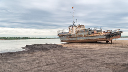 Old rusty ship on sand beach against river panorama at dawn. Solvychegodsk, Arkhangelsky region, Russia.
