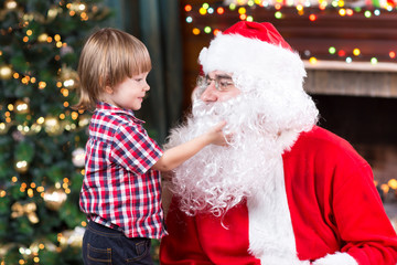 Surprised little boy looks at fake Santa Claus with fake beard sitting opposite Christmas tree