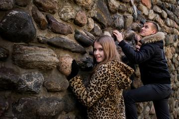 Молодые люди  на прогулке у каменистой стены.