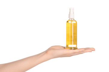 Massage and body care topic: a woman's hand holding a bottle of oil to the spa isolated on white background in studio