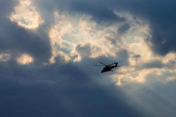 silhouette of a helicopter in the sun
