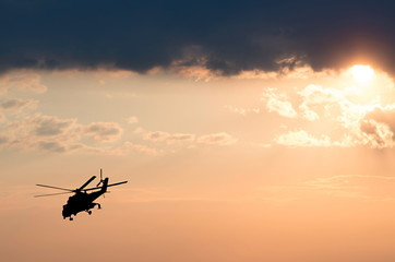 silhouette of the helicopter on the sunrise background