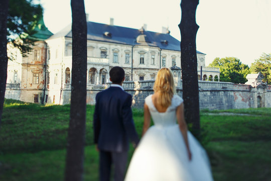 elegant bride in white dress and handsome groom holding hands in the forest in front of castle