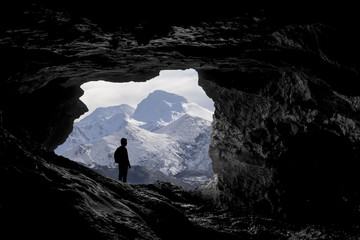 Alone traveller into a cave viewing a snowy mountain landscape,