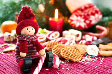 Wooden smiling doll with sweets on christmas background with can