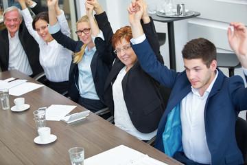 Geschäftsleute heben Hände zur Motivation