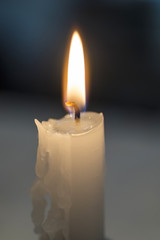 Candle glowing in a black background