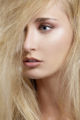 closeup  portrait of beautiful model with blond hair covering he