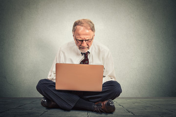 Business man thinking and sitting on the floor working on computer