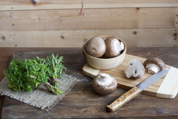 Champignon mushrooms, a knife, bagging and herbs on a wooden board on wooden background