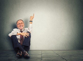 Senior happy man sitting on floor with legs crossed and pointing up