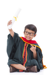 Happy boy in graduation suit on white background.