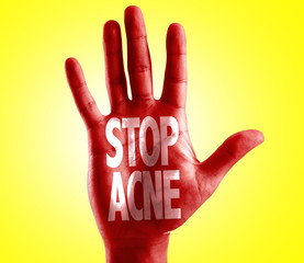 Stop Acne written on hand with yellow background