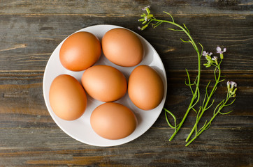 Eggs on white plate and wooden background