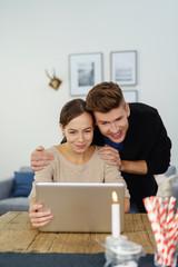 entspanntes junges paar sitzt am esstisch und schaut auf laptop