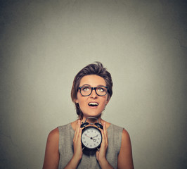 young smiling woman with alarm clock looking up