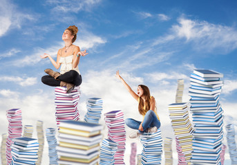 competitive young woman sitting on a books pile ascending to the