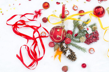 Christmas toys and jewelry on snow from candles