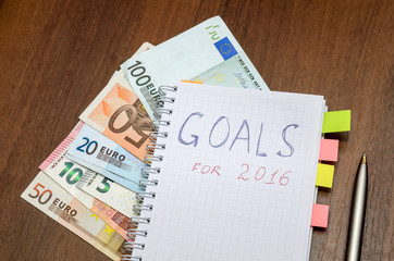 Notebook with text goals of year 2016 with dollar on wooden