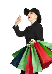 Happy woman in hat with paper bags on white background