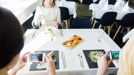 close up of women picturing food by smartphones