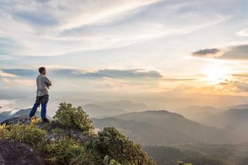 tourist man on top of a mountain enjoying valley view