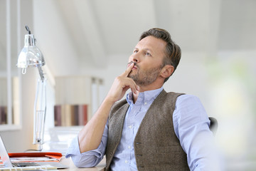 Man at work looking up with thoughtful look