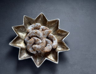 German Kipferl Cookies dusted with icing sugar on a star shaped plate against a grey background 5