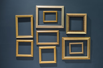 Golden classic picture frames on green wall