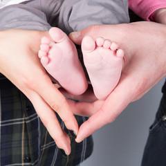 Newborn baby feet on female hands, shape like a lovely heart