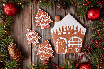 Christmas gingerbread house and fur tree cookies composition with xmas decorations on vintage wooden table background. Homemade traditional dessert food recipe