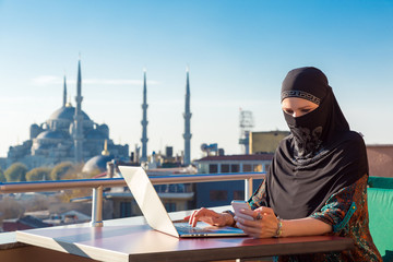 Traditionally dressed Muslim Woman working on computer at outdoor balcony with oriental urban landscape with minarets and blue sky on background