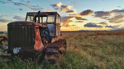 Old tractor in the field at sunset