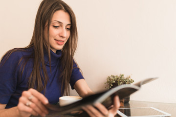 Woman in blue pullover reading journal in cafe