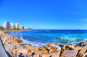The coast line of Limassol, Cyprus on a sunny day on the background of a clear blue sky through fisheye lens in HDR