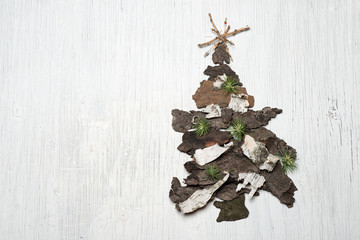 Christmas tree made of tree bark on retro background with space for text