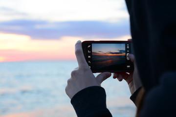Fototapeta Dziewczyna robi zdjęcie wschodu słońca swoim smartfonem obraz