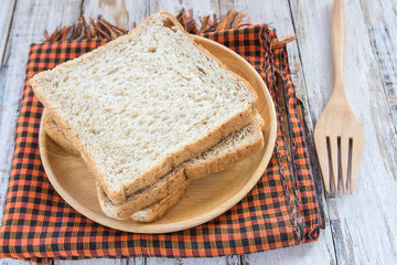 Whole wheat bread on wooden plate