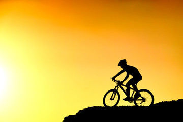 A cyclist riding down the hill with sunset silhouette