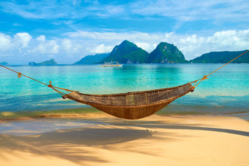 A hammock at the beach with the view of Bacuit Archipelago islands (El Nido, Philippines