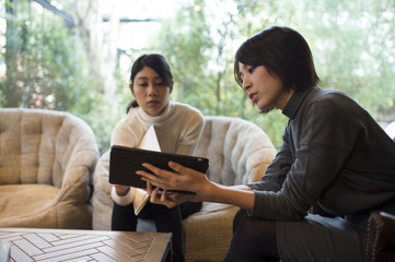 Women are talking while showing a tablet