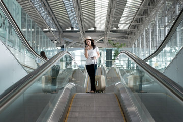 Young Asian woman with luggage down the escalator in airport.