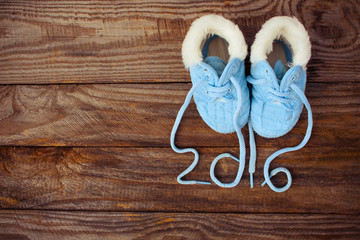 2016 year written laces of children's shoes on old wooden background. Toned image