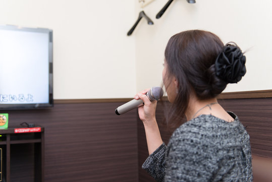ひとりでカラオケをしている日本人女性