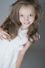 Portrait of a cute little girl in a white dress..