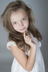 Portrait of a cute little girl in a white dress..